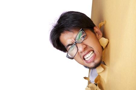 wanhopig: Mad zakenman dragen van een bril te breken door een papieren muur Stockfoto