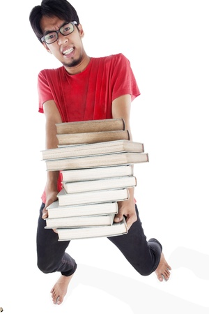 Portrait of a overwhelmed young student carrying a stack of heavy books photo