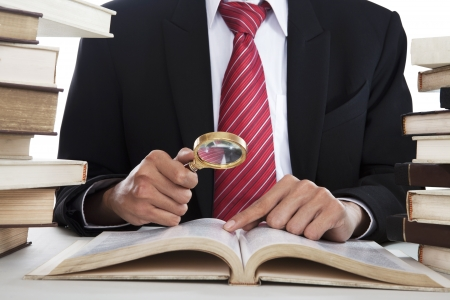 magnifying glass man: Businessman searching informations from the books by using magnifying