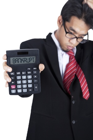 Businessman showing his bankruptcy on the calculator photo