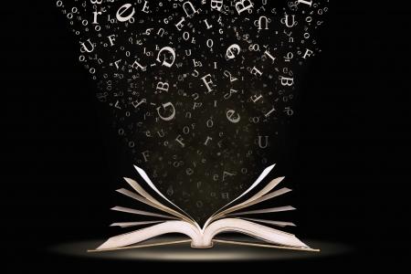 Een open boek met brieven vallen in de pagina's Stockfoto