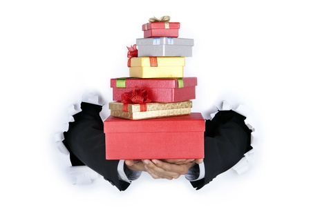 Businessman's hands holding gift boxes breaking through a paper wall photo