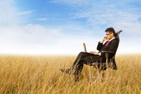 ofis koltuğu: Businessman on office chair working with a laptop outdoor