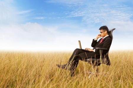 campi�a: Hombre de negocios en la silla de oficina que trabaja con un ordenador port�til al aire libre