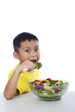 Child eating salad a over white background photo