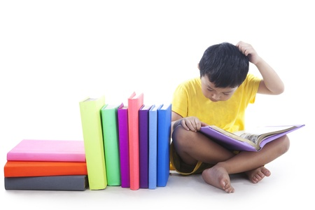 scratching head: Child reading the books and scratching his head, shot in studio isolated on white background Stock Photo