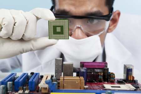 A scientist focusing at a chip of motherboard