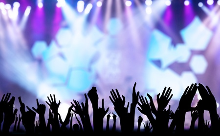 live happy: Photos of hands raised at rock concert, silhouetted against stage lighting. Stock Photo
