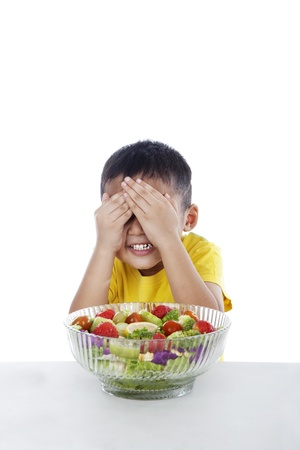 dislike: Boy refuses to eat salad by cover his eyes Stock Photo