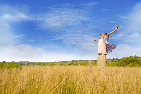 praise god: Man worshiping god shot at yellow grass Stock Photo