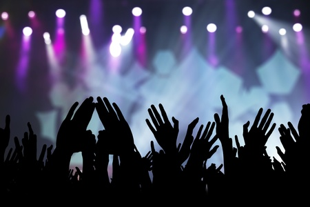 live on air: Photos of hands raised at rock concert, silhouetted against stage lighting. Stock Photo