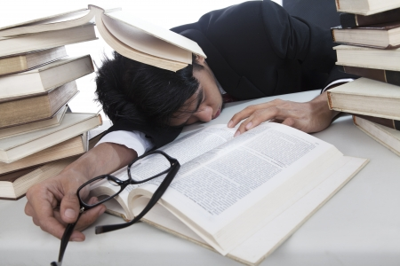 Overwhelmed businessman to read books sleeping in office photo