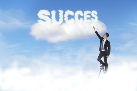 A businessman on a ladder reaching for the success photo