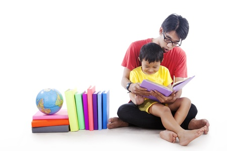 indonesian people: Little boy reading a geography book with dad shot in studio isolated on white