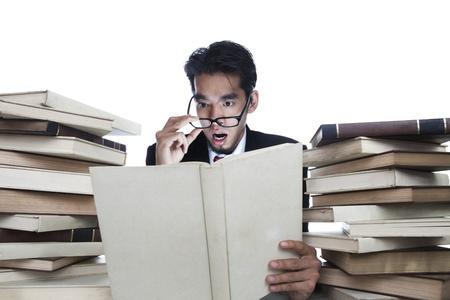 Shocked businessman reading books isolated on white photo