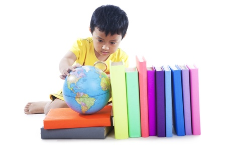 Boy studying geography with globe and books photo