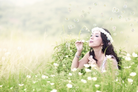 blowing bubbles: Young attractive happy woman blowing bubbles on the meadow Stock Photo