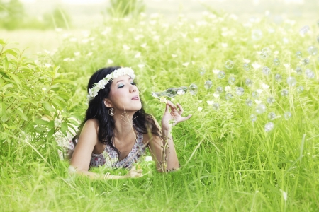 Asian woman wearing tiara playing with bubbles in meadow.  photo