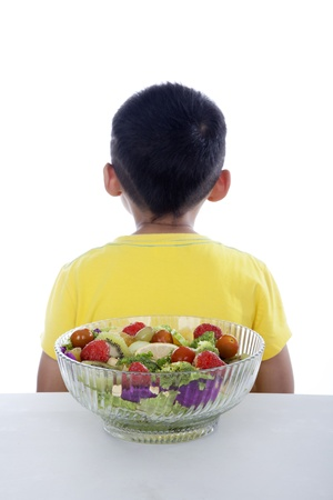 aversion: Boy turning his back to fruit and vegetable salad shot in studio isolated on white