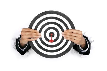 dart board: Businessman hand breaking through a paper wall holding a dart board Stock Photo