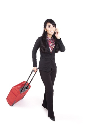 Asian businesswoman carrying suitcase while making a phone call photo