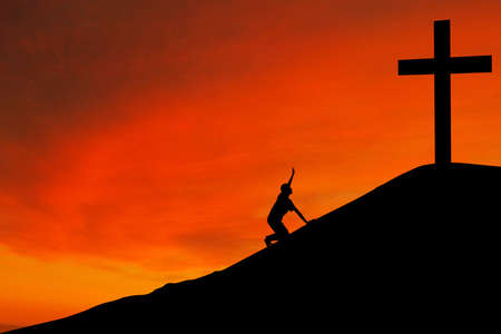 Christian background: Silhouette of man kneeling down by the cross photo