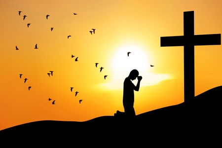 confession: Silhouette of a man praying under the cross at sunrise or sunset Stock Photo