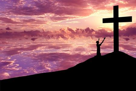 eucharistie: Contexte chrétienne: Silhouette de l'homme wroship s la croix au coucher du soleil ou le lever du soleil