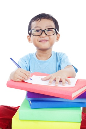 ni�os escribiendo: Lindo chico asi�tico con gafas estudiando un disparo en el estudio aislado en blanco Foto de archivo