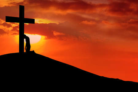 kneeling: Silhouette of a man with his head on the cross shot at sunrisesunset Stock Photo