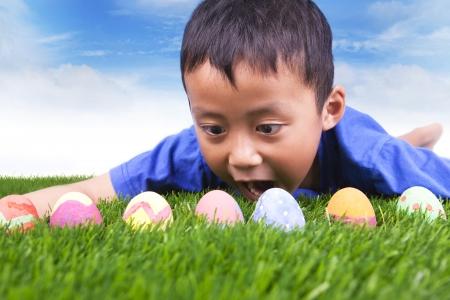 egg hunt: Easter egg hunt. Cute boy find easter eggs hidden in fresh green grass. Stock Photo