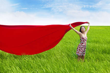 Asian woman holding a red scarf enjoying the day on a green field Stock Photo - 14683512
