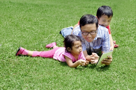 Happy family: Young father with his kids playing digital tablet outdoor photo