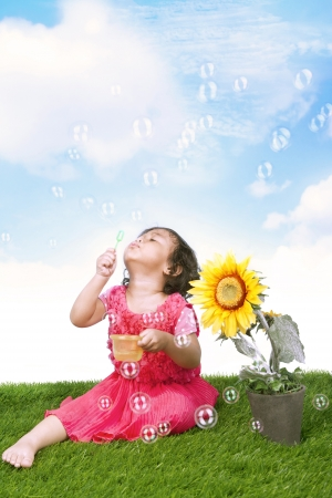 Girl blowing soap bubbles outdoors, shot under clear sky photo