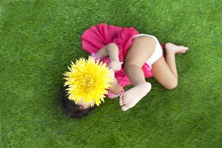underpants: Girl with gerbera flower lying on green grass, shot outdoor