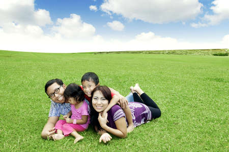 Happy family: Father, Mother, and their children. Shot outdoor in summer day photo