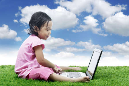 Happy cute girl plays with laptop. Shot outdoor over beautiful sky photo