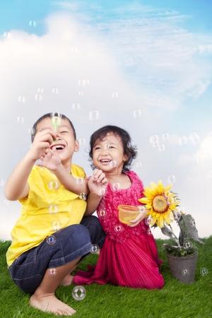 soap bubbles: Gl�ckliche Geschwister spielen Seifenblasen auf dem gr�nen Rasen