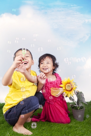 Happy sibling playing soap bubbles on the green grass photo
