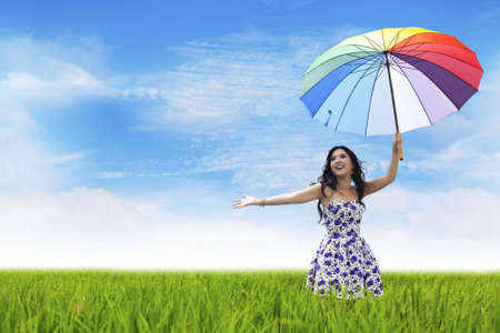 paddy fields: Pretty woman carrying colorful umbrella having fun on a field