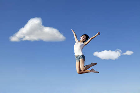 Joyful asian woman jumping over blue sky photo