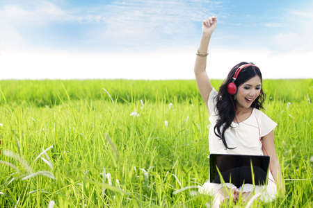 Asian woman enjoying summer by listens to digital music on her laptop outdoor photo