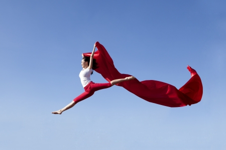 Young asian woman jumping with red scarf shot over clear blue sky Фото со стока