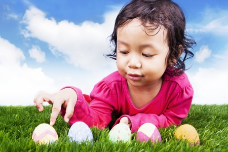 Cute girl counting easter eggs using her finger on the green grass