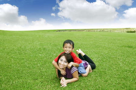piggyback: Beautiful Asian mother smiling with her cute son in meadow Stock Photo