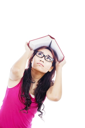 Portrait of afraid college student covering her head by textbook. shot in studio Stock Photo - 14683073