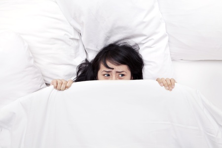 is astonished: Afraid young woman hiding in white blanket, shot in bedroom  Stock Photo