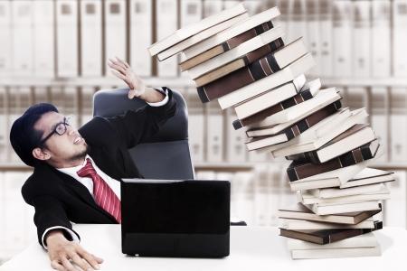 accidente laboral: Hombre de negocios asustado con la pila de libros que a punto de derrumbarse. Disparo en la oficina Foto de archivo