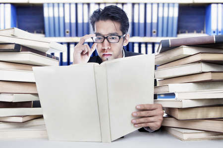 Young businessman analyzing business books at office photo
