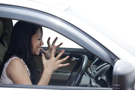 road rage: Angry female driver driving a car isolated on white